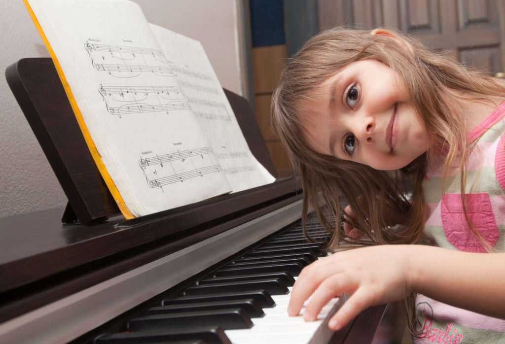 smiling girl at piano 1024x698 1 - کلاس پیانو